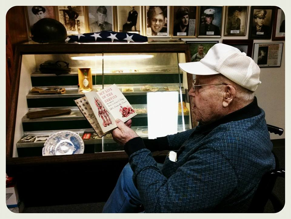 Side view of man sitting looking at book, he is wearing a blue shirt and white hat