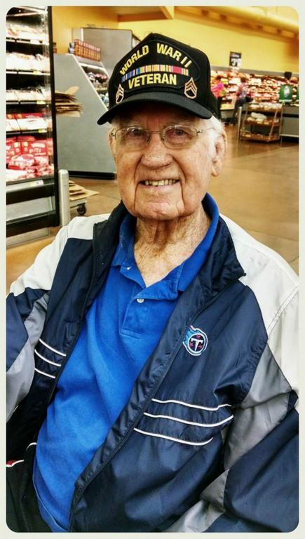 Portrait of veteran at the grocery store, wearing blue shirt, glasses, and World War II hat