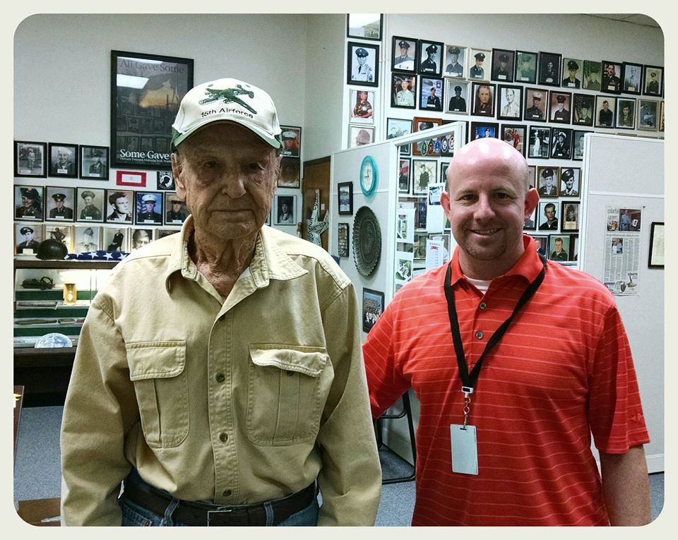 Image of Nathan Weinbaum standing and smiling beside man in khaki shirt and 15th Airforce hat