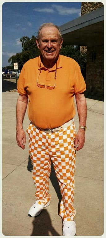Man in orange shirt and orange and white checked pants smiles into camera