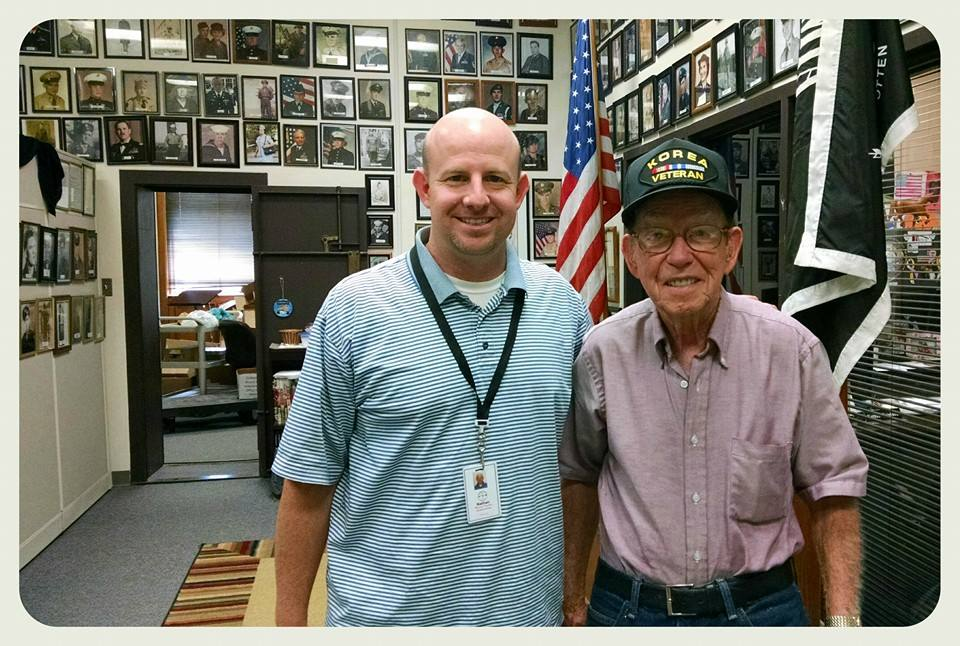 At the Veterans Affairs office, Nathan Weinbaum stands with man wearing oxford shirt and Korea Veteranhat