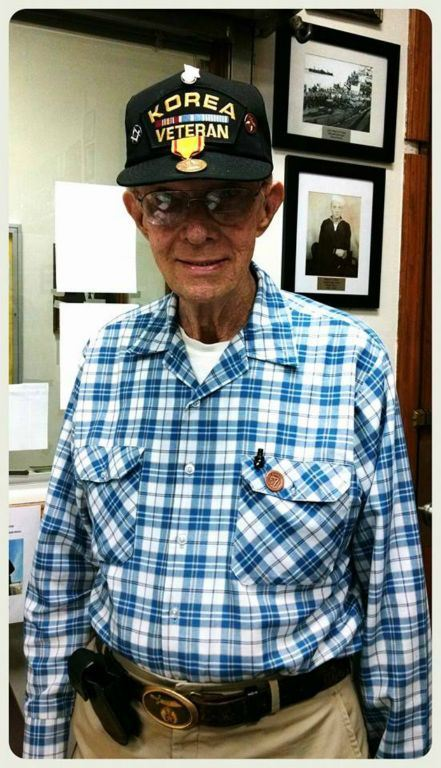 Portrait of man, standing, wearing blue plaid shirt, glasses, and Korea Veteran hat