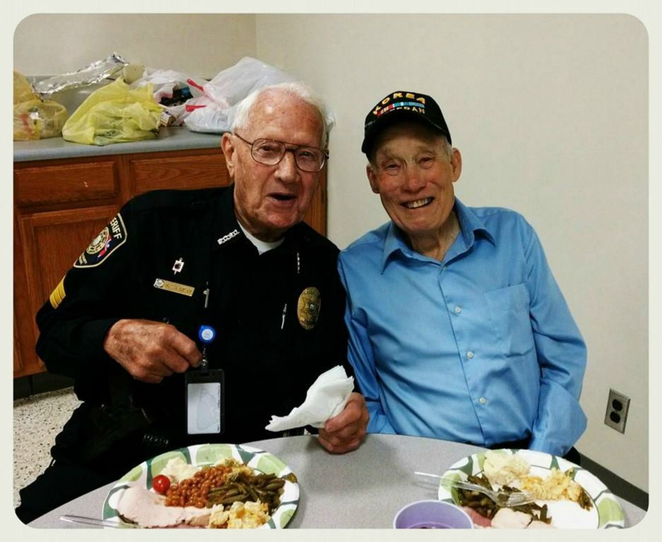 Sheriff in uniform leans into smile with friend wearing Korea Veteran hat, both are at a table with a plate in front of them
