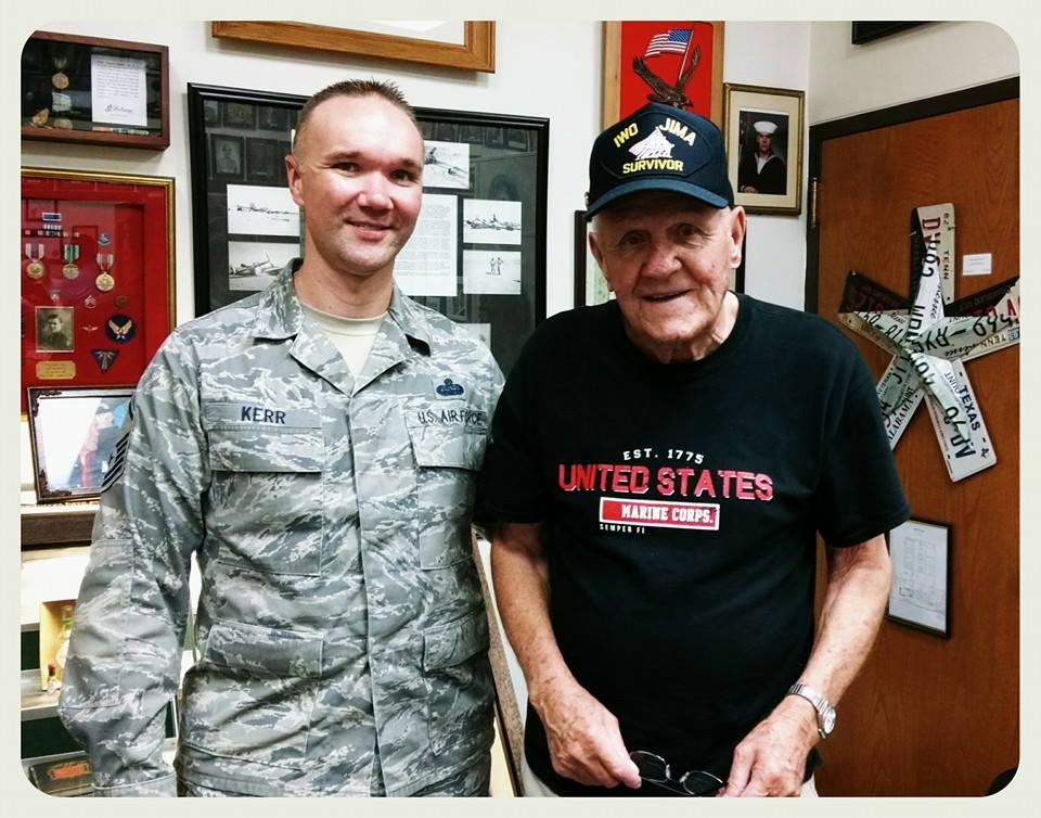 Active Duty Air Force soldier standing beside man in black shirt, with black hat that says Iwo Jima Survivor
