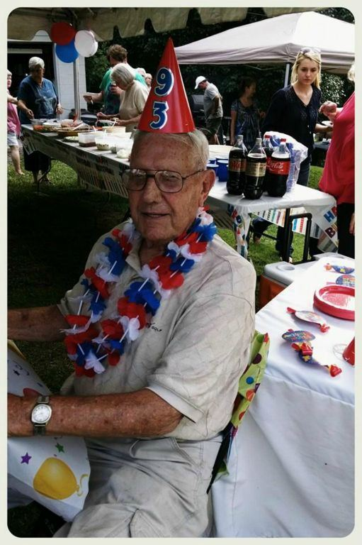 Picture of man wearing red, white, and blue lei, and a party hat with the number 93 on it