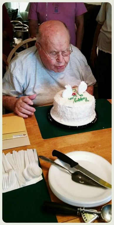 Image of man blowing out numbered candles on a cake, 96