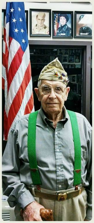 Veteran wearing VFW cap and green suspenders looks into camera