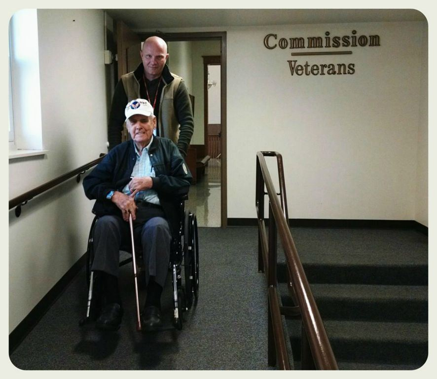 Young man pushes veteran in wheelchair in hallway, both are looking into the camera smiling