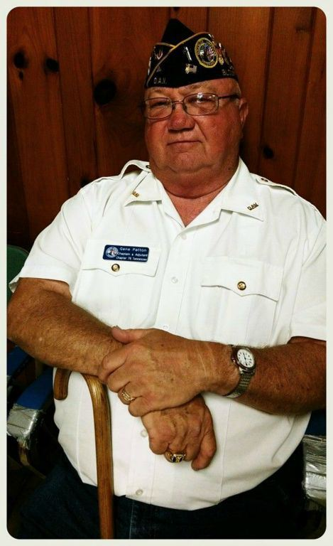 Portrait of sitting veteran wearing white shirt and glasses, looking into camera