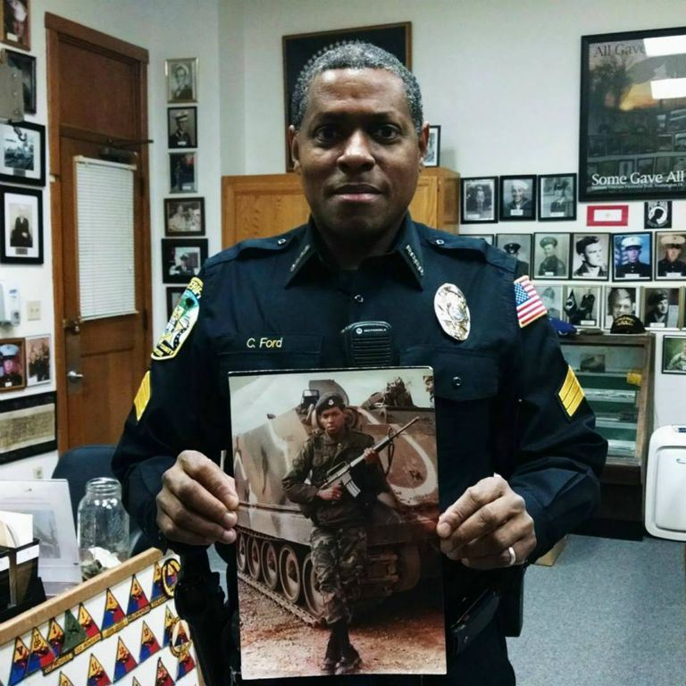 Police Officer holds self portrait from military service, looking into camera