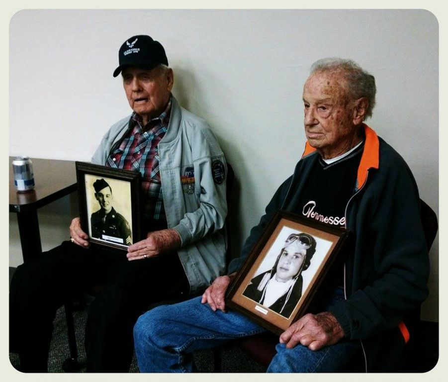 Two men sitting beside each other, both holding self portraits from military service