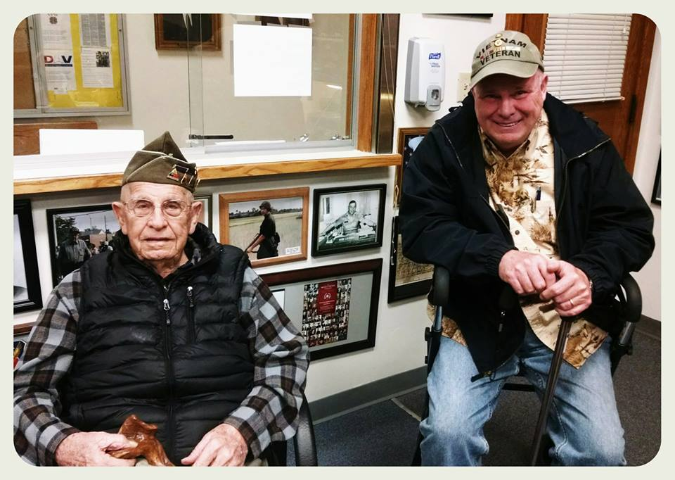 Two sitting veterans, looking into camera, one is smiling