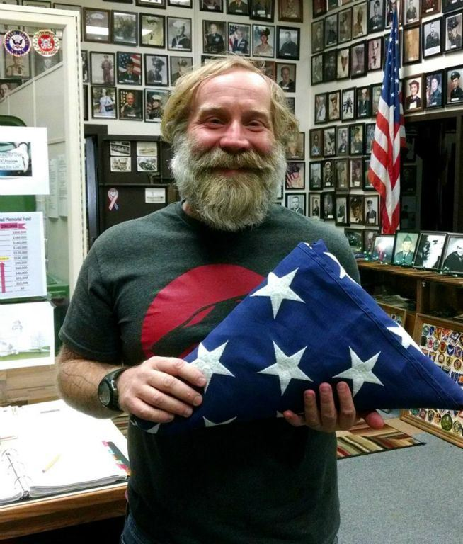 Smiling man holds up folded American flag