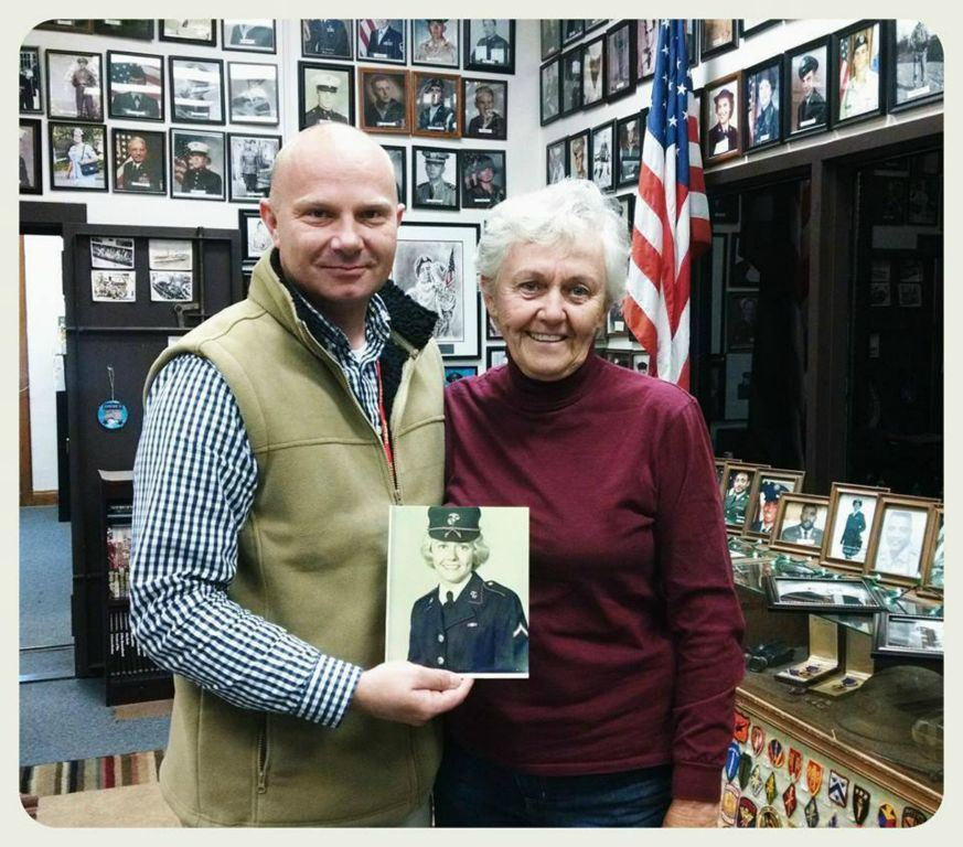Young man stands holding portrait of woman beside him from her military service