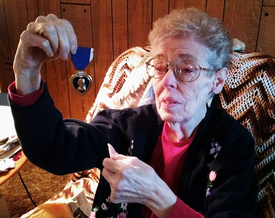 Woman, sitting in chair wearing black sweater and glasses, holds up purple heart medal