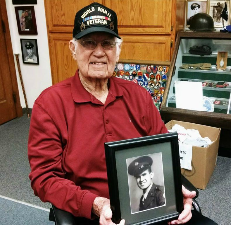 Man in red shirt and World War II Veteran hat holds military service portrait