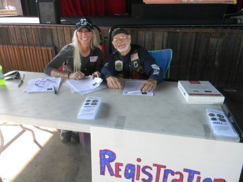Woman in black shirt and black hat smiles with man in black shirt and black hat, sitting behind registration table