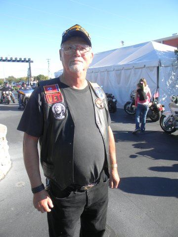 Man in black pants, shirt, and black leather vest, glasses, and black hat stands in parking lot in front of motorcycles