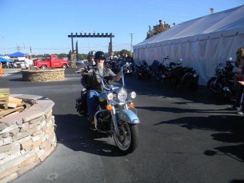 Motorcyclist rides blue bike in lot in front of white tent