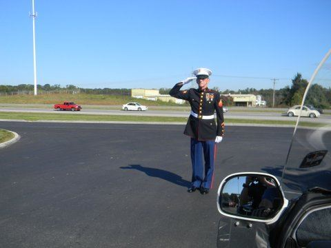 Marine in dress uniform salutes vehicle from road