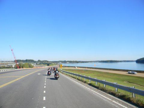 Image of motorcycles in front on road with grass on sides