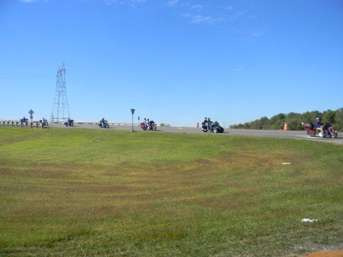 Image of grassy curve in road with line of motorcycles