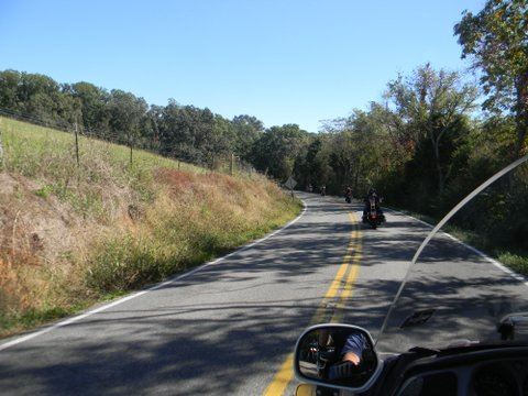 Image taken from motorcycle of motorcycles in front on road with trees on sides