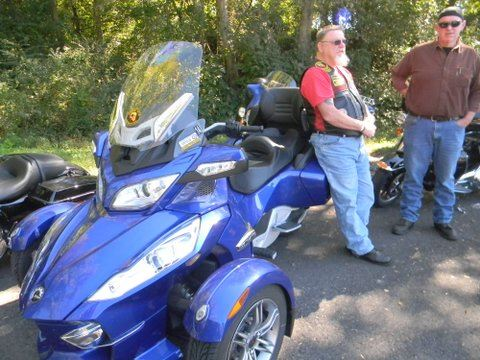Man leans against blue colored three wheeled motorcycle in parking lot