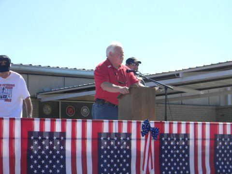 Man in red shirt speaking at podium