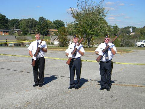 Three men in white shirts with black pants, holding rifles to their chests